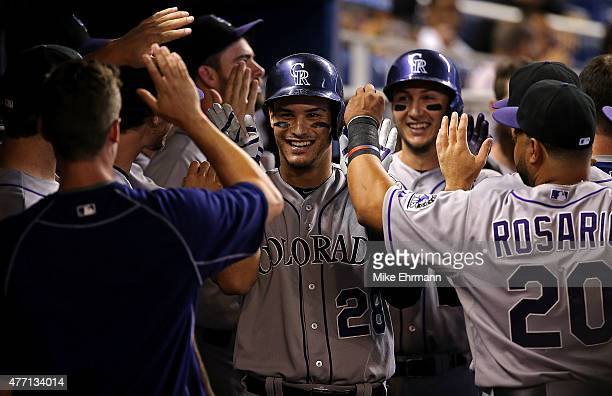 Nolan Arenado of the Colorado Rockies is congratulated after hitting a two run home run during a game against the Miami Marlins at Marlins Park on...