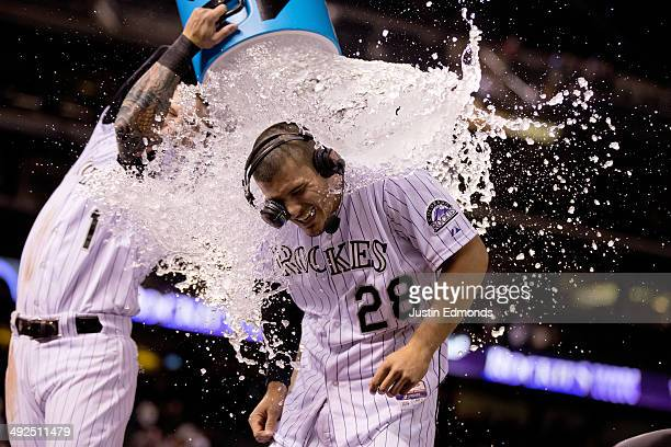 Nolan Arenado of the Colorado Rockies is doused with water by Brandon Barnes after his game winning hit in the ninth inning against the San Francisco...