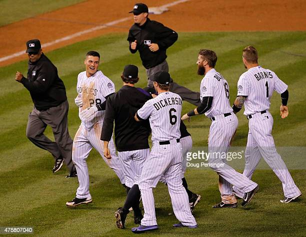 Nolan Arenado of the Colorado Rockies is mobbed by his teammates after he produced the game winning RBI with a sacrifce fly to defeat the Los Angeles...