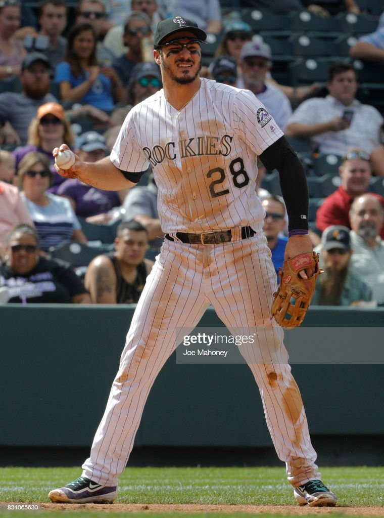 Nolan Arenado #28 of the Colorado Rockies looks to throw to first base after fielding a ground ball hit by Lane Adams #16 of the Atlanta Braves that struck Arenado in the wrist forcing him from the game in the seventh inning at Coors Field on August 17, 2017 in Denver, Colorado.