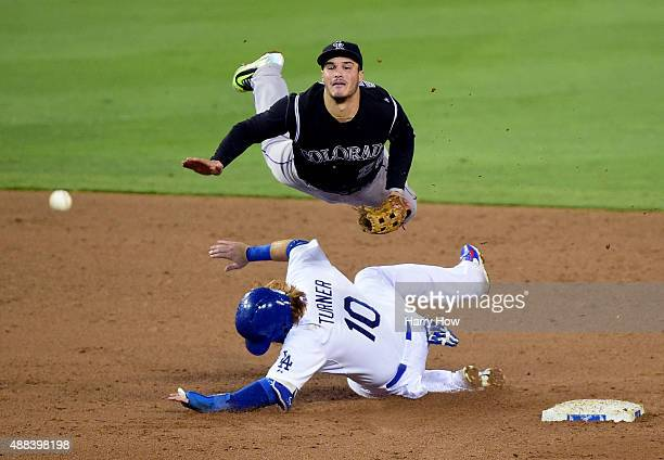 Nolan Arenado of the Colorado Rockies makes a throw over Justin Turner of the Los Angeles Dodgers for a double play during the fourth inning at...