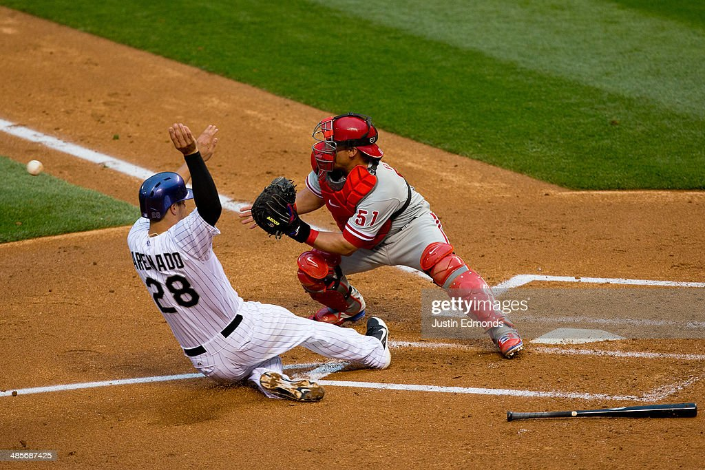 Nolan Arenado of the Colorado Rockies slides in to score as catcher Carlos Ruiz of the Philadelphia Phillies receives the throw during the third...