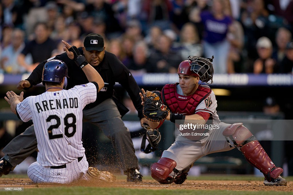 Nolan Arenado of the Colorado Rockies slides safely into home plate to score ahead of the tag by catcher Miguel Montero of the Arizona Diamondbacks...