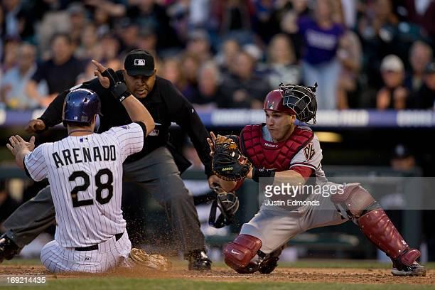 Nolan Arenado of the Colorado Rockies slides safely into home plate to score ahead of the tag by catcher Miguel Montero of the Arizona Diamondbacks...
