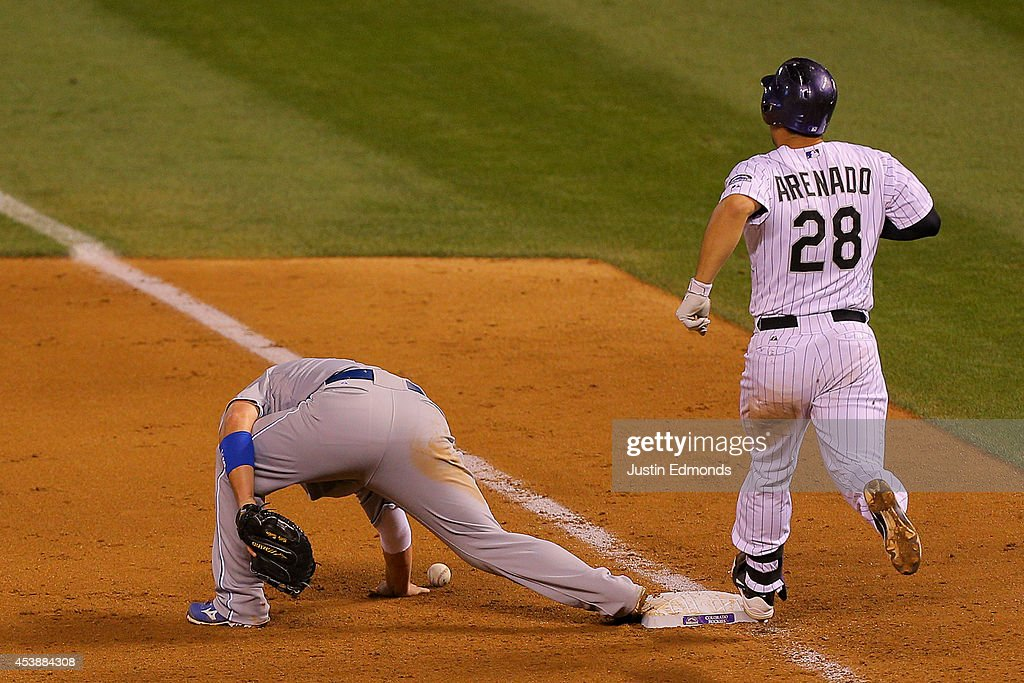 <a gi-track='captionPersonalityLinkClicked' href=/galleries/search?phrase=Nolan+Arenado&family=editorial&specificpeople=7934273 ng-click='$event.stopPropagation()'>Nolan Arenado</a> #28 of the Colorado Rockies strides into first base safely as first baseman <a gi-track='captionPersonalityLinkClicked' href=/galleries/search?phrase=Billy+Butler&family=editorial&specificpeople=759092 ng-click='$event.stopPropagation()'>Billy Butler</a> #16 of the Kansas City Royals is unable to make the play on a throwing error by third baseman Christian Colon (not pictured) at Coors Field on August 20, 2014 in Denver, Colorado. The Rockies defeated the Royals 5-2.
