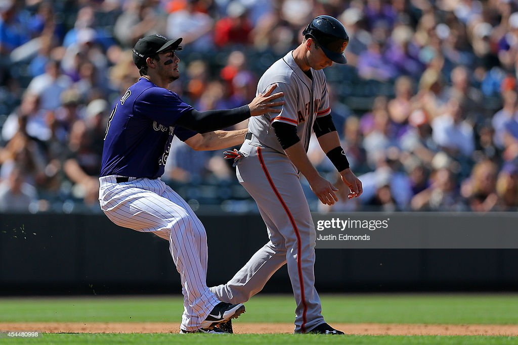 <a gi-track='captionPersonalityLinkClicked' href=/galleries/search?phrase=Nolan+Arenado&family=editorial&specificpeople=7934273 ng-click='$event.stopPropagation()'>Nolan Arenado</a> #28 of the Colorado Rockies tags out <a gi-track='captionPersonalityLinkClicked' href=/galleries/search?phrase=Buster+Posey&family=editorial&specificpeople=4896435 ng-click='$event.stopPropagation()'>Buster Posey</a> #28 of the San Francisco Giants for the third out of the eighth inning at Coors Field on September 1, 2014 in Denver, Colorado. The teams were resuming a game previously suspended in the sixth inning on May 22 due to rain.