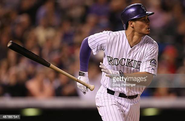 Nolan Arenado of the Colorado Rockies tosses his bat as he heads for first base on a single off of Carlos Torres of the New York Mets in the seventh...