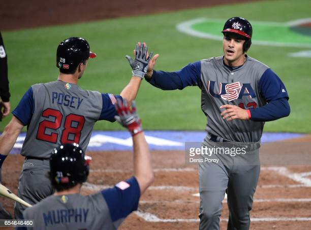 Nolan Arenado of the United States right is congratulated by Buster Posey of the United States after scoring during the second inning of the World...