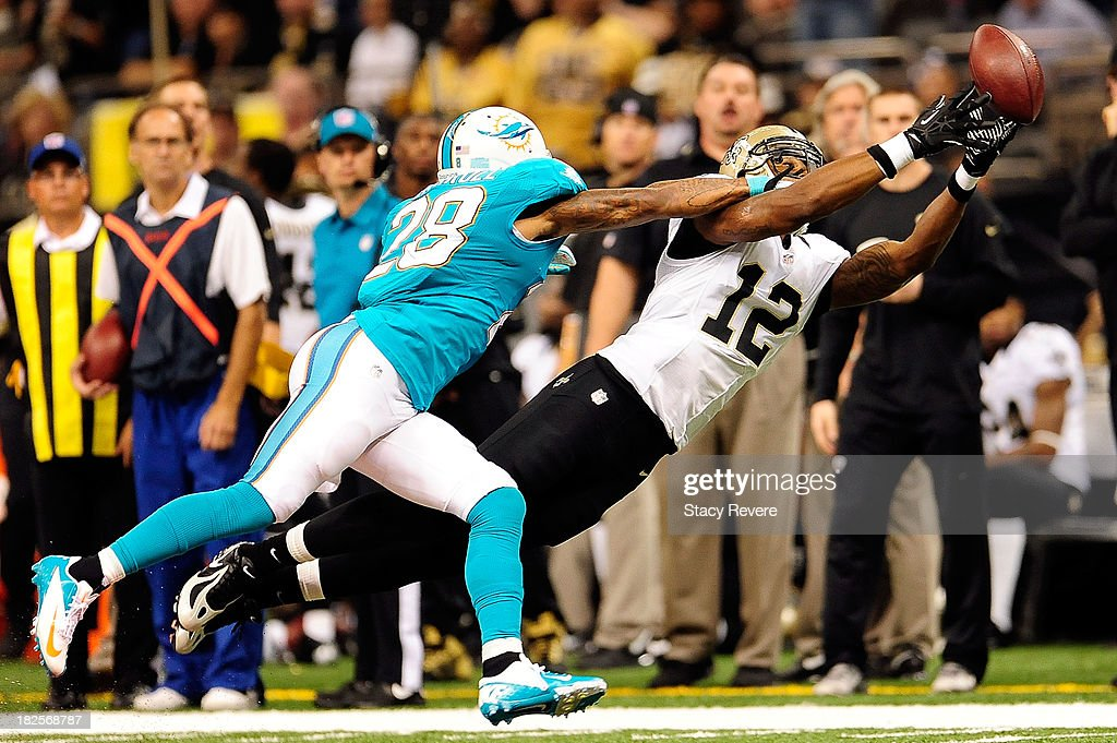 <a gi-track='captionPersonalityLinkClicked' href=/galleries/search?phrase=Nolan+Carroll&family=editorial&specificpeople=5574471 ng-click='$event.stopPropagation()'>Nolan Carroll</a> #28 of the Miami Dolphins defends a pass intended for <a gi-track='captionPersonalityLinkClicked' href=/galleries/search?phrase=Marques+Colston&family=editorial&specificpeople=741430 ng-click='$event.stopPropagation()'>Marques Colston</a> #12 of the New Orleans Saints during a game at the Mercedes-Benz Superdome on September 30, 2013 in New Orleans, Louisiana. The Saints defeated the Dolphins 38-17.