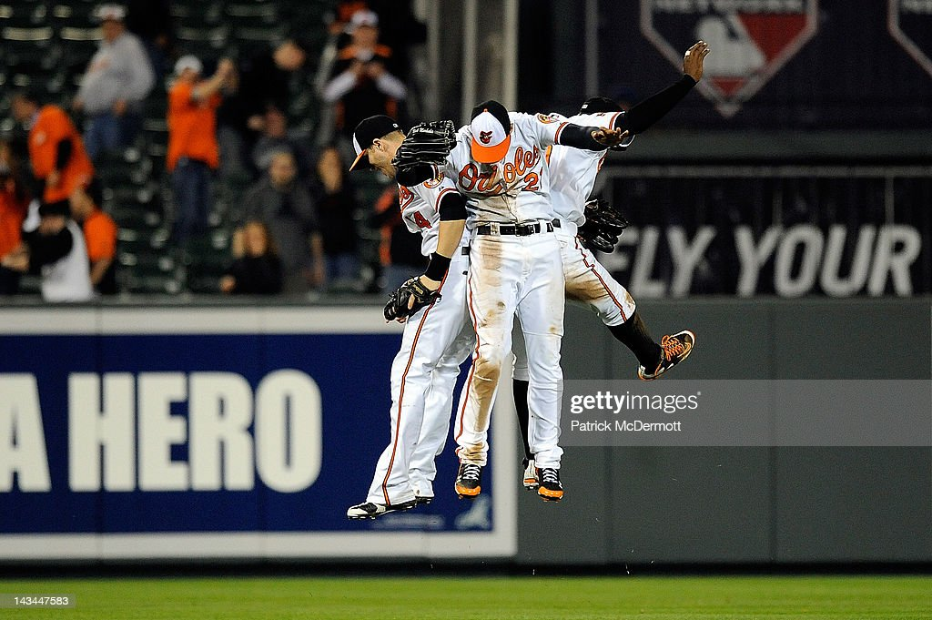 Nolan Reimold Nick Markakis and Adam Jones of the Baltimore Orioles celebrate after defeating the Toronto Blue Jays at Oriole Park at Camden Yards on...
