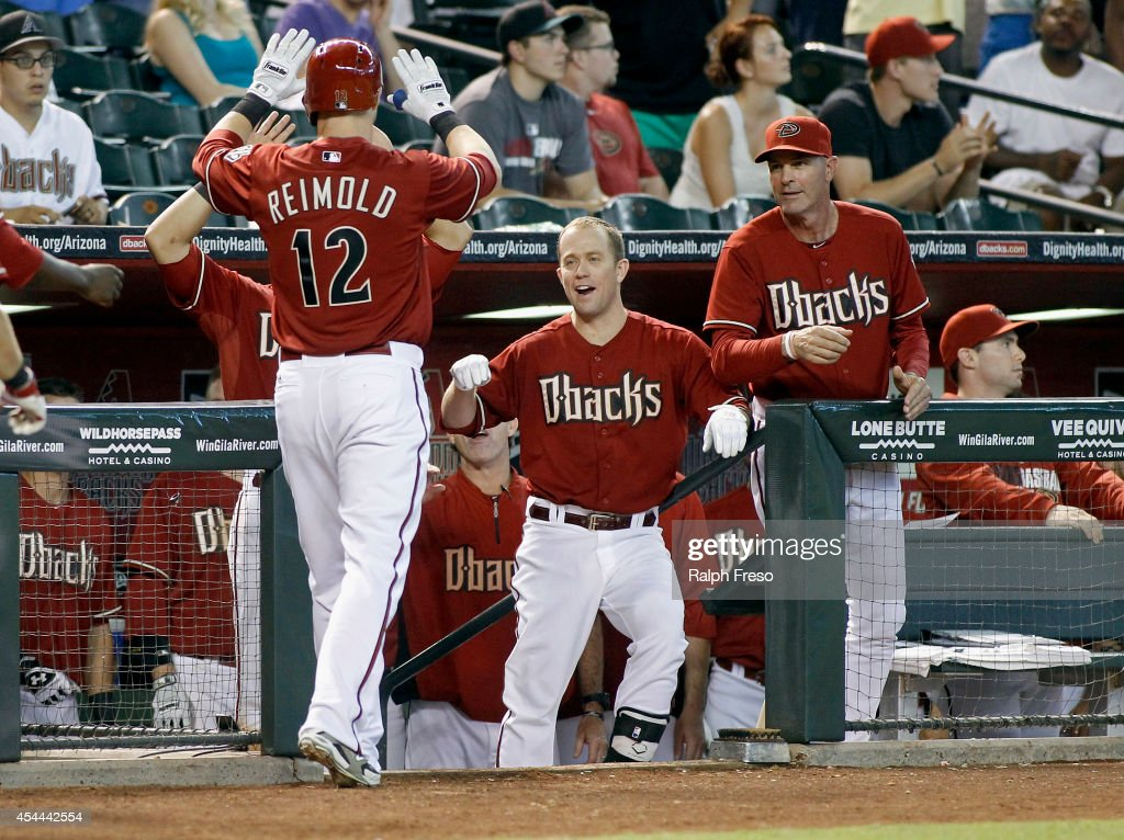 <a gi-track='captionPersonalityLinkClicked' href=/galleries/search?phrase=Nolan+Reimold&family=editorial&specificpeople=757348 ng-click='$event.stopPropagation()'>Nolan Reimold</a> #12 of the Arizona Diamondbacks is congratulated by teammates David Peralta #6 (L), <a gi-track='captionPersonalityLinkClicked' href=/galleries/search?phrase=Aaron+Hill+-+Baseball+Player&family=editorial&specificpeople=239242 ng-click='$event.stopPropagation()'>Aaron Hill</a> #2 (C) and manager <a gi-track='captionPersonalityLinkClicked' href=/galleries/search?phrase=Kirk+Gibson&family=editorial&specificpeople=207042 ng-click='$event.stopPropagation()'>Kirk Gibson</a> #23 after his two-run home run against the Colorado Rockies during the seventh inning of a MLB game at Chase Field on August 31, 2014 in Phoenix, Arizona.