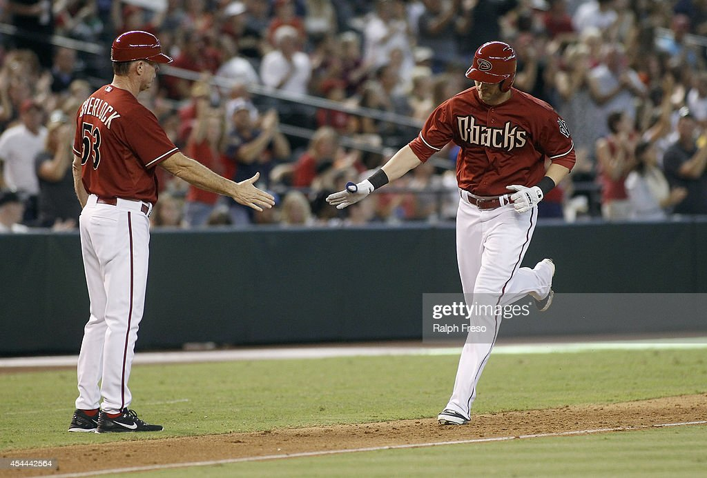 <a gi-track='captionPersonalityLinkClicked' href=/galleries/search?phrase=Nolan+Reimold&family=editorial&specificpeople=757348 ng-click='$event.stopPropagation()'>Nolan Reimold</a> #12 of the Arizona Diamondbacks (R) is congratulated by third base coach Glenn Sherlock #53 after his two-run home run against the Colorado Rockies during the seventh inning of a MLB game at Chase Field on August 31, 2014 in Phoenix, Arizona.