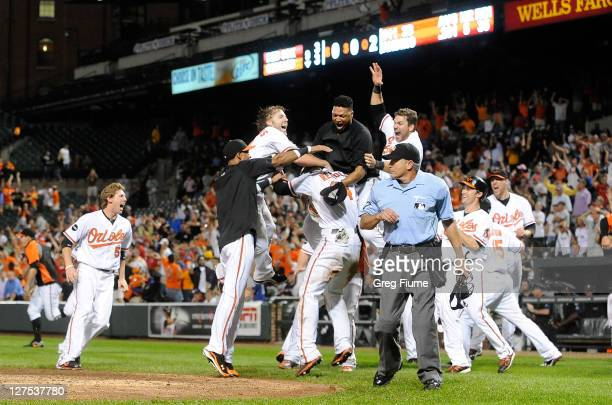 Nolan Reimold of the Baltimore Orioles is mobbed by teammates after scoring the game winning run in the ninth inning against the Boston Red Sox at...