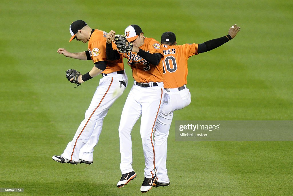 Nolan Reimold #14, Ryan Flaherty #3 and Adam Jones #10 of the Baltimore Orioles celebrate a win after a baseball game against the Oakland Athletics at Oriole Park at Camden Yards on April 28, 2012 in Baltimore, Maryland. The Orioles won 10-1.
