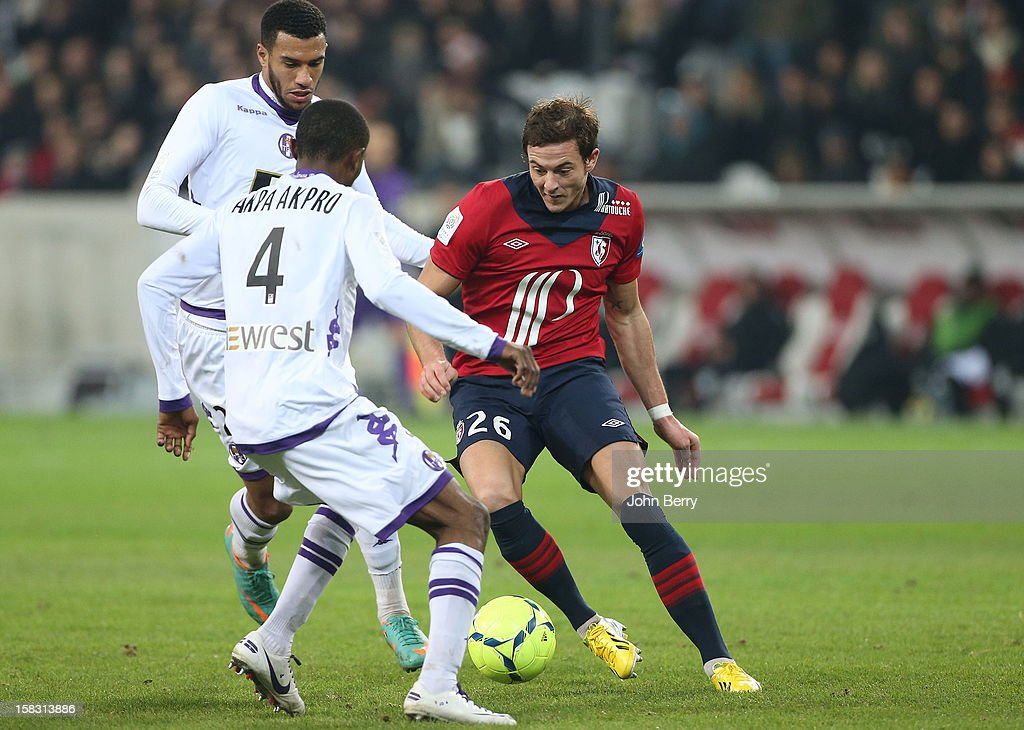 <a gi-track='captionPersonalityLinkClicked' href=/galleries/search?phrase=Nolan+Roux&family=editorial&specificpeople=5969784 ng-click='$event.stopPropagation()'>Nolan Roux</a> of LOSC tries to dribble <a gi-track='captionPersonalityLinkClicked' href=/galleries/search?phrase=Etienne+Capoue&family=editorial&specificpeople=809639 ng-click='$event.stopPropagation()'>Etienne Capoue</a> and Jean Daniel Akpa Akpro of Toulouse FC during the French Ligue 1 match between Lille OSC and Toulouse FC at the Grand Stade Lille Metropole on December 11, 2012 in Lille, France.