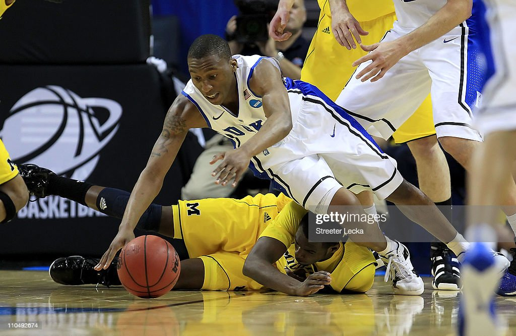<a gi-track='captionPersonalityLinkClicked' href=/galleries/search?phrase=Nolan+Smith&family=editorial&specificpeople=4215916 ng-click='$event.stopPropagation()'>Nolan Smith</a> #2 of the Duke Blue Devils dives for the ball over Tim Hardaway Jr. #10 of the Michigan Wolverines in the first half during the third round of the 2011 NCAA men's basketball tournament at Time Warner Cable Arena on March 20, 2011 in Charlotte, North Carolina.