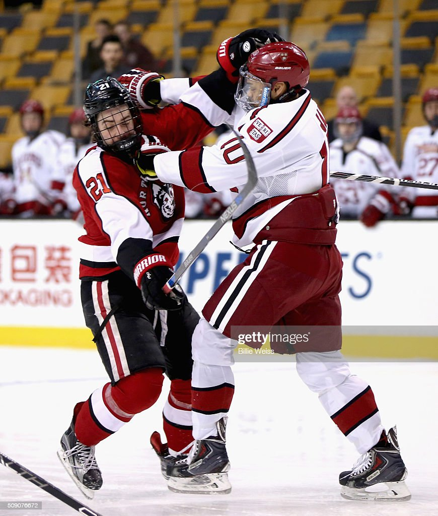 Nolan Stevens #21 of Northeastern University is pushed by Brayden Jaw #10 of Harvard University during the first period of the Beanpot Tournament consolation game at TD Garden on February 8, 2016 in Boston, Massachusetts.