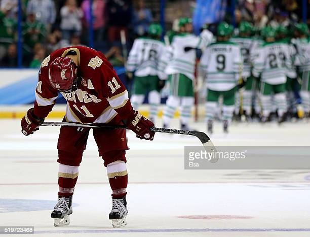 Nolan Zajac of the Denver Pioneers reacts to the loss as the North Dakota Fighting Hawks celebrate the win during semifinals of the 2016 NCAA...