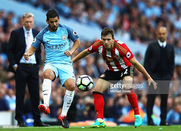 Nolito of Manchester City passes the ball while Donald Love of Sunderland watches on during the Premier League match between Manchester City and...