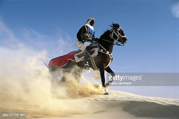Nomad riding horse, trailing sand cloud, low angle view