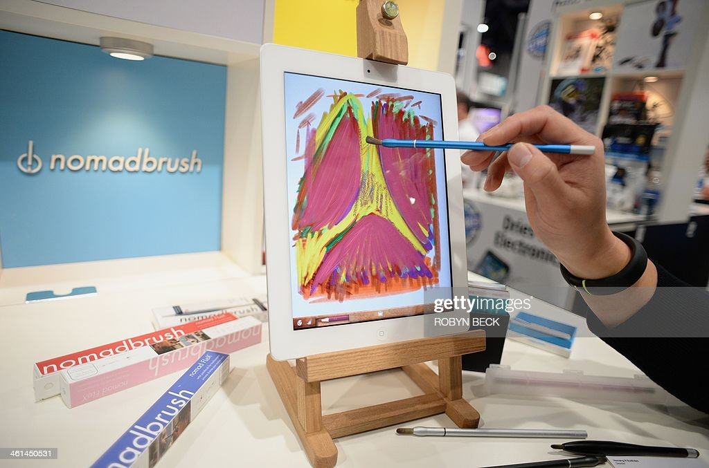 NomadBrush founder and CEO Don Lee uses a NomadBrush Flex paintbrush stylus and an oil painting app to paint on an iPad at the 2014 International CES in Las Vegas, Nevada, January 8, 2014. Each bristle of the paintbrush stylus, which was recently released and is priced at USD $29, is conductive. AFP PHOTO / Robyn Beck