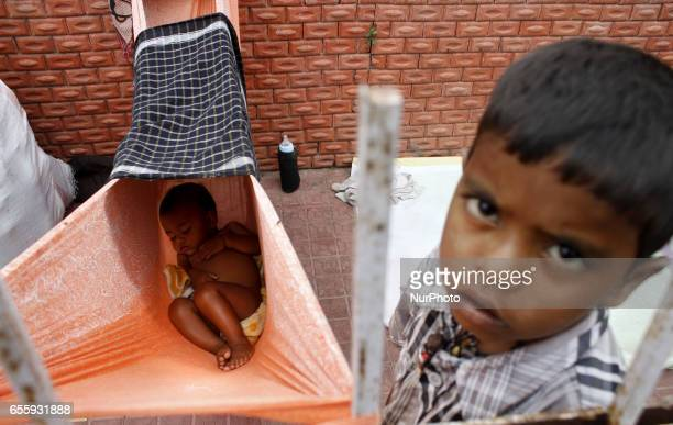 A nomadic baby sleeps in a hang made by its mothers cloth on way side in an hot afternoon in the eastern Indian city Bhubaneswar on March 21 2017