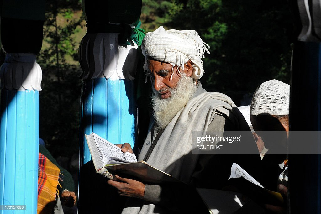 A nomadic Kashmiri Muslim recites the Koran outside the shrine of Miyan Peer in Baba Nagri, about 44 km northeast of Srinagar, on June 8, 2013. Hundreds of devotees thronged the shrine of Miyan Peer, a revered Muslim saint of the nomadic Gujjar tribe, to observe his 121st death anniversary. AFP PHOTO/Rouf BHAT