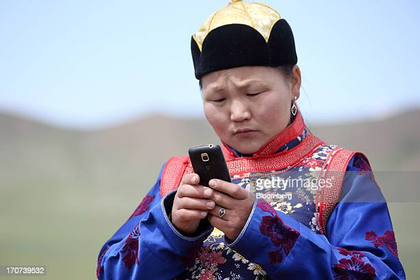 A nomadic woman wearing traditional clothing uses a smartphone in Zammar Mongolia on Wednesday June 12 2013 Mongolia is scheduled to start operations...