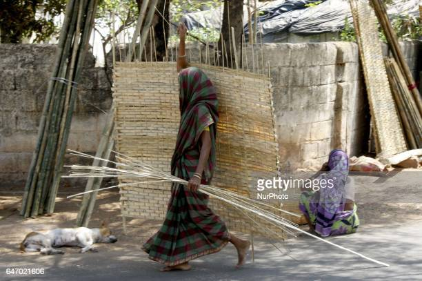 Nomadic women look near to their living place as they are busy to make bamboo accessories on wayside and sale it to people to earn money to maintain...