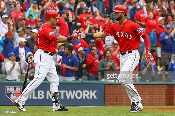 Nomar Mazara of the Texas Rangers celebrates with Carlos Beltran after scoring against the Toronto Blue Jays in the fourth inning of game two of the...