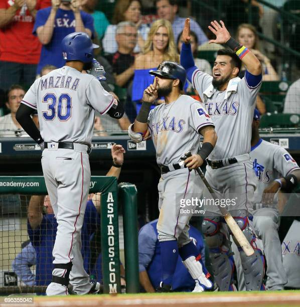 Nomar Mazara of the Texas Rangers receives congratulations from Rougned Odor and Robinson Chirinos after hitting a threerun home run in the eighth...