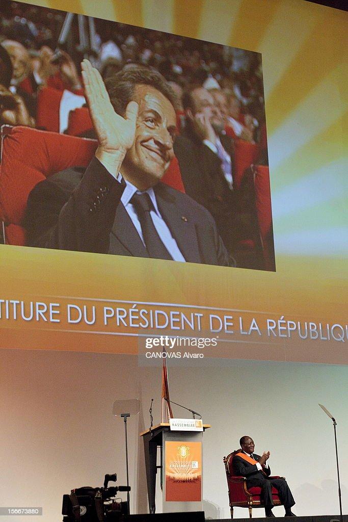 Nomination Of <a gi-track='captionPersonalityLinkClicked' href=/galleries/search?phrase=Alassane+Ouattara&family=editorial&specificpeople=697562 ng-click='$event.stopPropagation()'>Alassane Ouattara</a>. Samedi 21 mai, Alassane OUATTARA a été investi chef de l'Etat ivoirien à YAMOUSSOUKRO, la ville natale du 'père de la nation', Félix HOUPHOUET-BOIGNY : le nouveau président ivorien sur scène, assis dans un fauteuil, applaudissant lors de la cérémonie. Au-dessus de lui, un écran géant avec Nicolas SARKOZY à l'image, souriant, le saluant de la main.