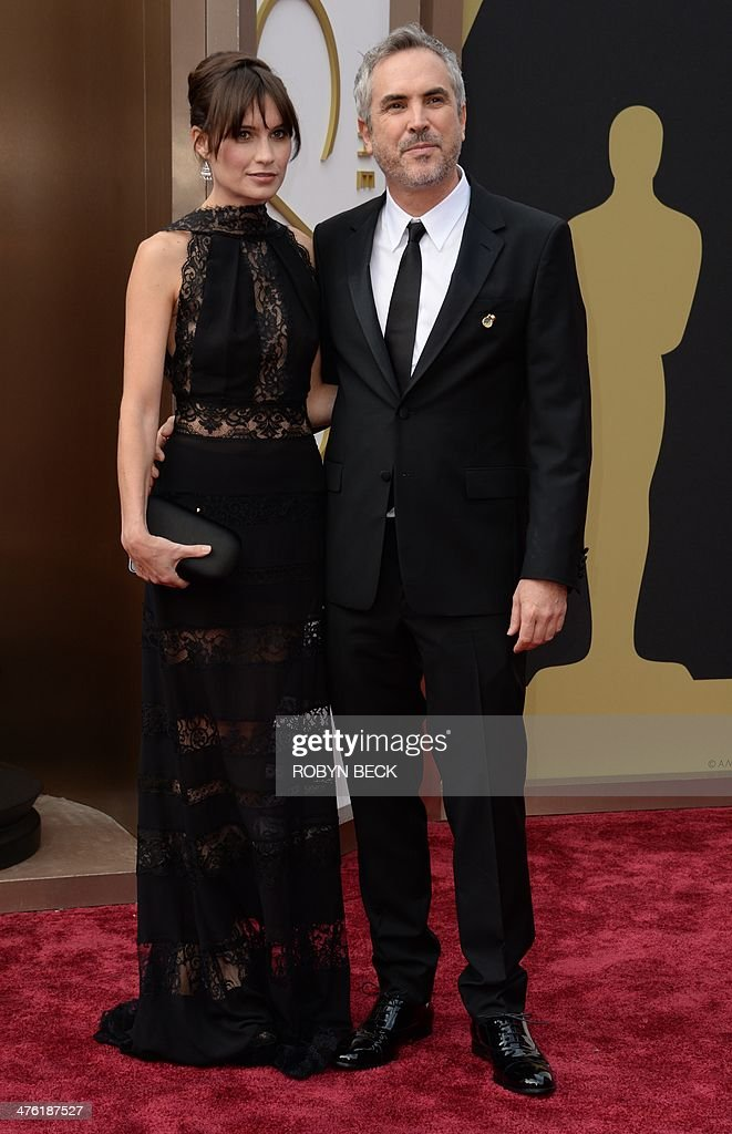 Nominee for Best Director 'Gravity' Alfonso Cuarón (r) and Sheherezade Goldsmith arrives on the red carpet for the 86th Academy Awards on March 2nd, 2014 in Hollywood, California. AFP PHOTO / Robyn BECK