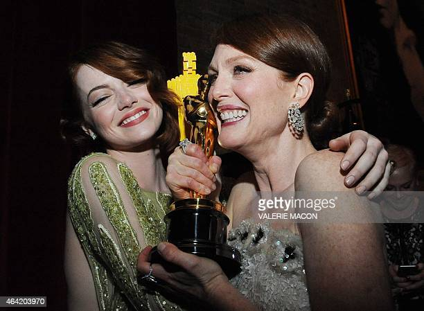 Nominee for Best Supporting Actress Emma Stone embraces Winner for Best Actress Julianne Moore at the Governor's Ball following the 87th Oscars...