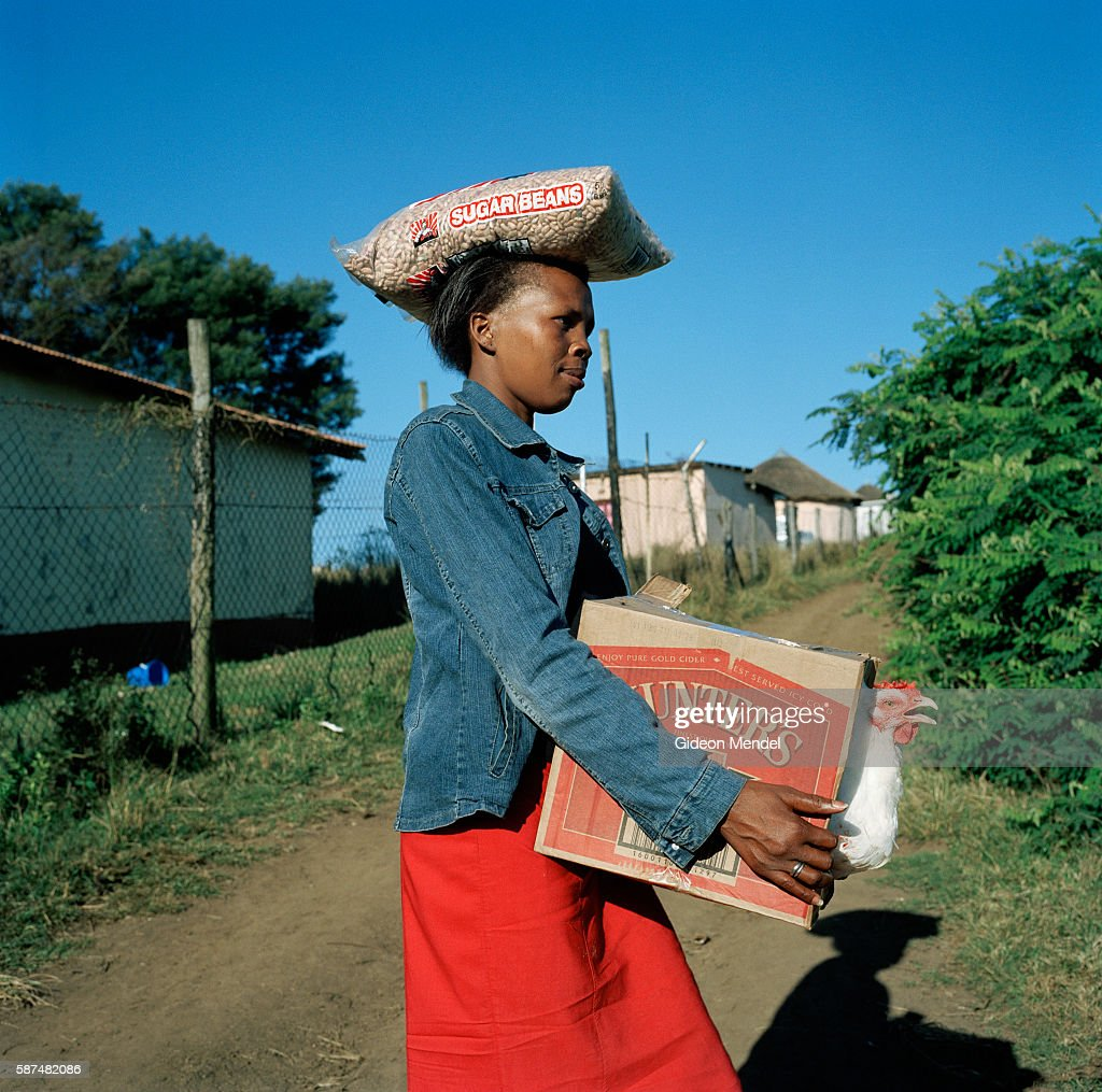 Nomphilo Mazuza aged 27 whose life has been saved by antiretroviral medication carries her shopping including a live chicken back to her home She...