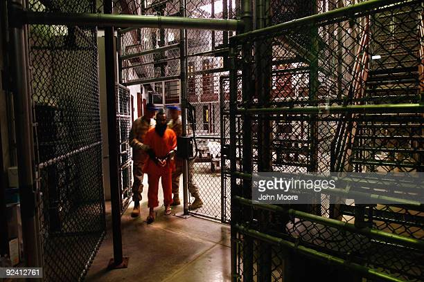 A 'noncompliant' detainee is escorted by guards after showering inside the US military prison for 'enemy combatants' on October 27 2009 in Guantanamo...