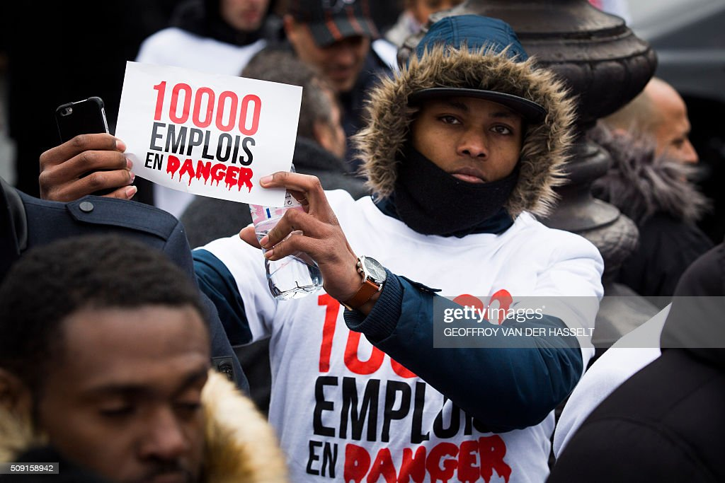 A non-licensed private hire cab drivers, known in France as VTC (voitures de tourisme avec chauffeur or tourism vehicles with chauffeur), holds a placard reading '10,000 jobs in danger' at the Place de la Nation during a protest on February 9, 2016. VTC drivers continued a fifth day of protests on February 9 against measures granted by the French prime minister to taxi drivers. / AFP / Geoffroy Van der Hasselt