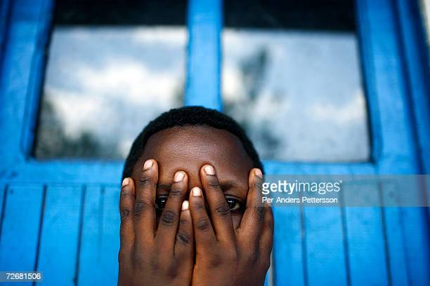 Nonmume Alitteee age 18 a victim of a horrible gang rape by five men hides her face as she poses for this portriat at the Ndosho center on October 4...
