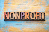 nonprofit banner - word abstract in vintage letterpress printing blocks stained by color inks