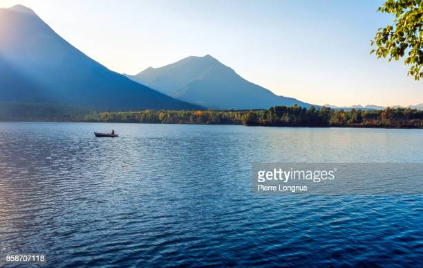 Non-recognizable person rowing on Kathlyn Lake in late afternoon, in the shadow of Hudson Bay Mountain, near Smithers, British Columbia, Canada