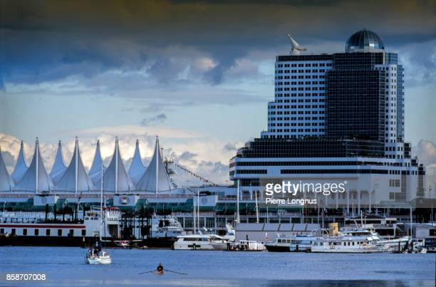 nonrecognizable rower in Burrard inlet under summer stormy skies, view on Canada place and Cruise ship and yacht Terminal in Background, Vancouver, British Columbia, Canada