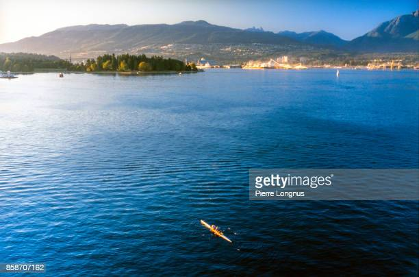 nonrecognizable rowers in Burrard inlet, Stanley Park in background, Vancouver, British Columbia, Canada