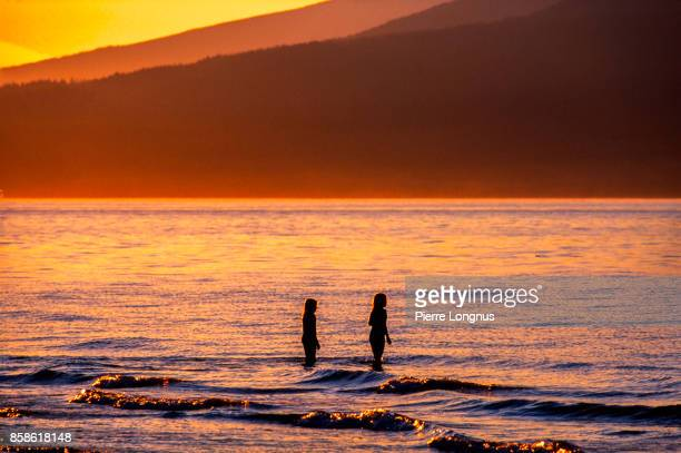 nonrecognizable young girls playing in the sea at sunset, Kitsina Beach, Vancouver, British Columbia, Canada