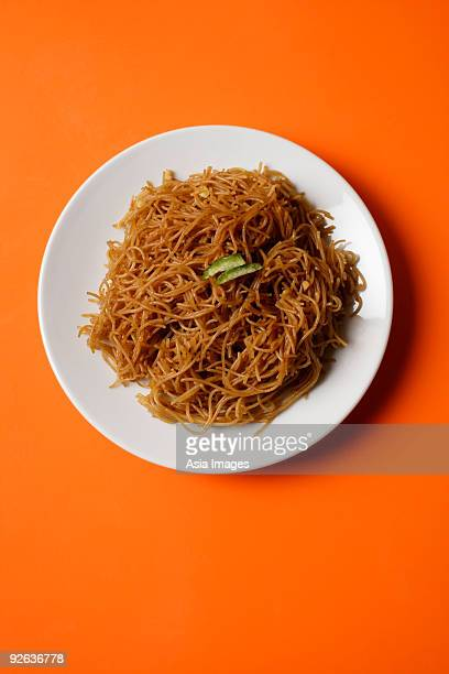 Noodles on plate on orange place mat.