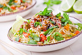 Bowl of thai noodles with pork and fresh vegetables