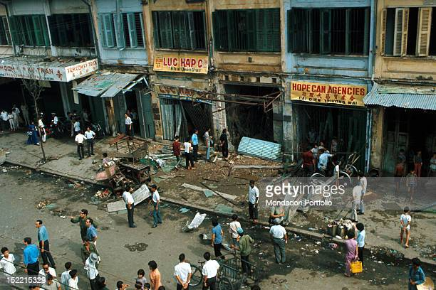 Noone was excluded from the bombardment not even the central parts of the city here a crowd of Vietnamese check the damage in Nauyen Cong Tru Street...