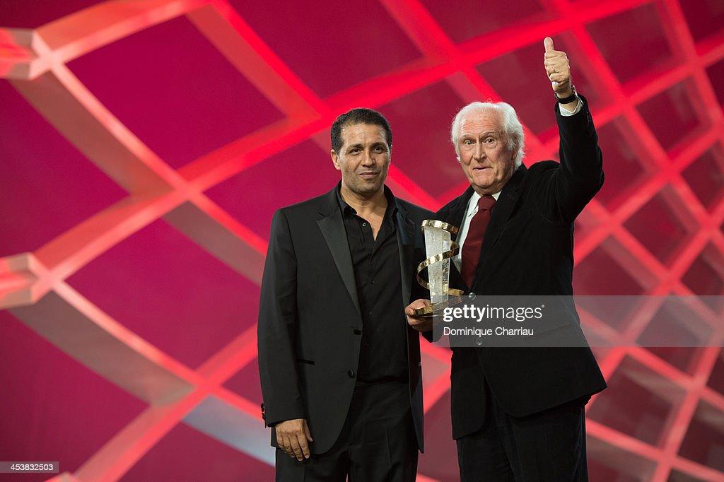 Noor-Eddine Lakhmari gives a tribute award to Fernando Solanas during the 13th Marrakech International Film Festival on December 5, 2013 in Marrakech, Morocco.