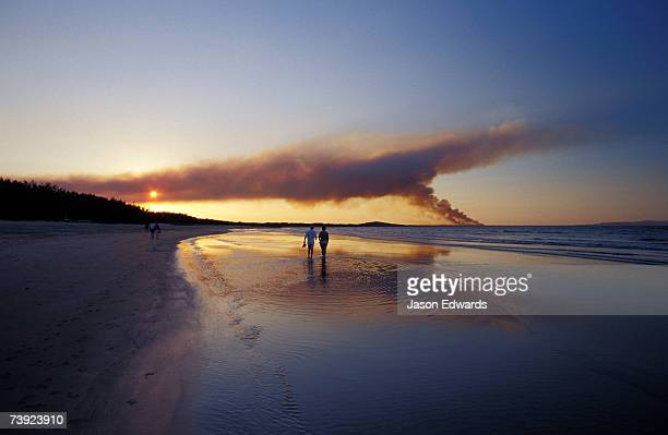 A couple walking on the beach at sunset, with a distant bush fire.