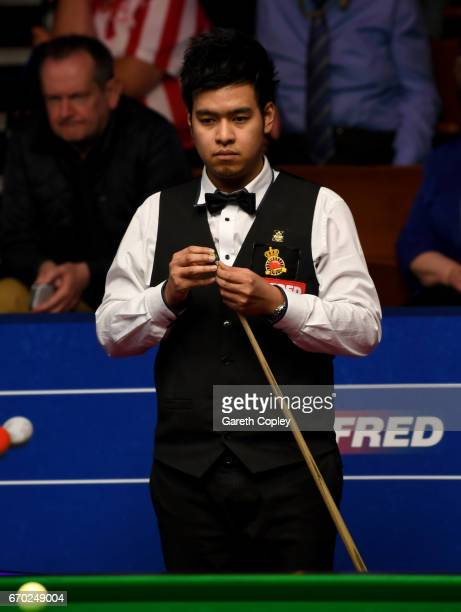 Noppon Saengkham lines up a shot against Neil Robertson during their first round match of the World Snooker Championship at Crucible Theatre on April...