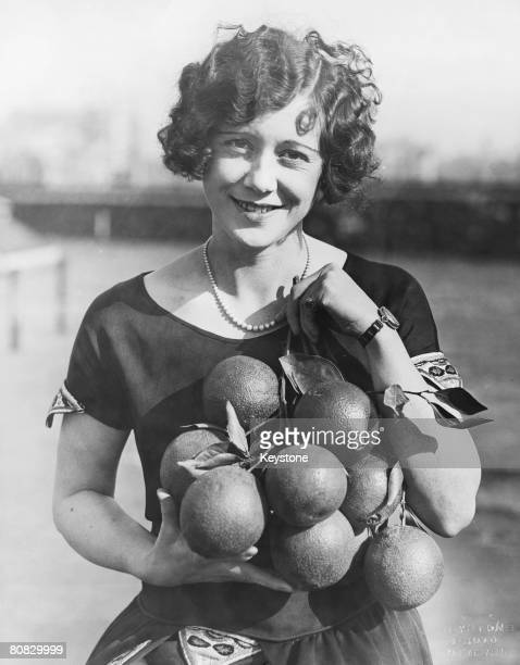 Nora Beger fof Los Angeles with the ten naval oranges she recieved as a gift from a California fruit grower circa 1915